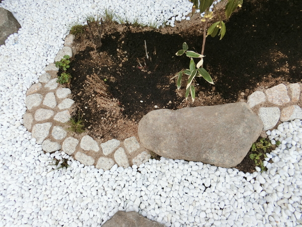 以前からやってみたかったごろた石を埋め込んだだけの土止め。  ポイントは目地幅なん