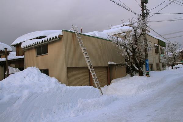 はしごをかけて車庫の雪下ろし開始です。  2/8半分済みました。   近所の車庫が雪